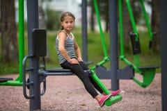 小女孩坐在操场的一个公开教练员机器 体育运动 免版税库存图片