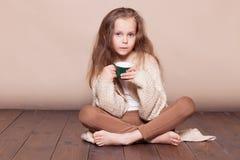 小女孩坐地板和饮用的茶 库存照片