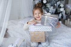 小女孩坐地板在与圣诞节礼物的圣诞树附近在手上 库存图片