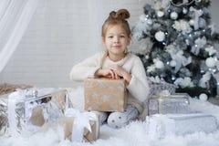 小女孩坐地板在与圣诞节礼物的圣诞树附近在手上 免版税图库摄影