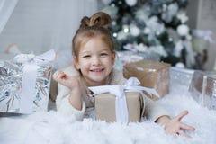小女孩坐地板在与圣诞节礼物的圣诞树附近在手上 图库摄影