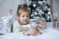 小女孩坐地板在与圣诞节礼物的圣诞树附近在手上 免版税库存照片