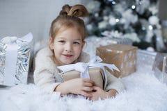 小女孩坐地板在与圣诞节礼物的圣诞树附近在手上 免版税库存图片