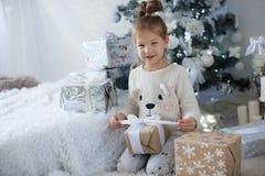 小女孩坐地板在与圣诞节礼物的圣诞树附近在手上 库存照片
