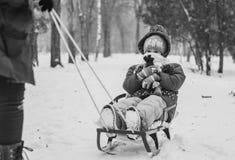 小女孩坐她的雪橇 库存照片