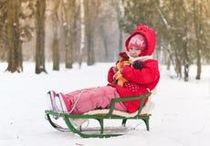 小女孩坐她的雪橇 免版税库存图片