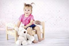 小女孩坐拿着长毛绒玩具的床 免版税库存照片