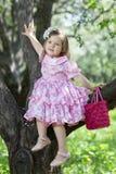 小女孩坐树 免版税图库摄影