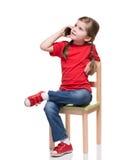 小女孩坐椅子和告诉由smartphone 库存照片