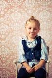 小女孩坐椅子 免版税库存照片