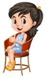 小女孩坐椅子 免版税图库摄影