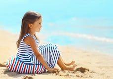 小女孩坐沙子海滩在海附近在夏天 库存照片