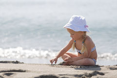小女孩坐海滩 免版税图库摄影