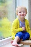 小女孩坐的下一个窗在雨天 免版税库存照片
