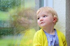 小女孩坐的下一个窗在雨天 库存照片