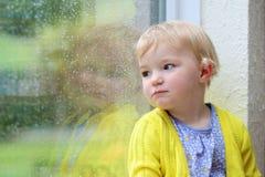 小女孩坐的下一个窗在雨天 图库摄影