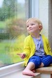 小女孩坐的下一个窗在雨天 免版税库存图片