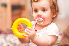 小女孩坐的使用与玩具圆环 免版税库存照片