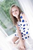 小女孩坐窗口 库存照片