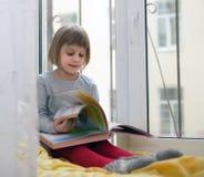小女孩坐舒适窗台 免版税库存照片