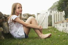 小女孩坐草在围场 免版税库存照片