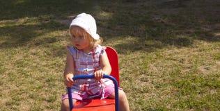 小女孩坐跷跷板 图库摄影