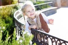 小女孩坐长凳,秋天时间 库存图片