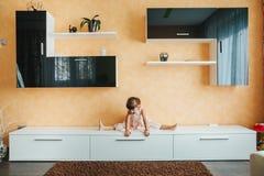 小女孩坐麻线在家具分裂了 瑜伽 免版税库存图片