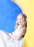 小女孩坐黄色月亮 免版税图库摄影