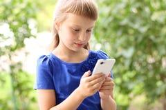 小女孩夏天公园谈话在电话,在一件蓝色礼服 白肤金发 免版税库存图片