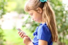 小女孩夏天公园谈话在电话,在一件蓝色礼服 白肤金发 图库摄影