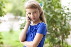 小女孩夏天公园谈话在电话,在一件蓝色礼服 白肤金发 免版税库存照片