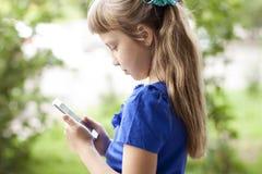 小女孩夏天公园谈话在电话,在一件蓝色礼服 白肤金发 免版税图库摄影