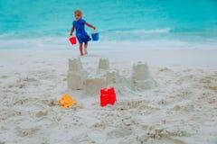 小女孩大厦在海滩的沙子城堡 库存图片