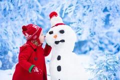 小女孩大厦雪人在冬天 免版税库存图片