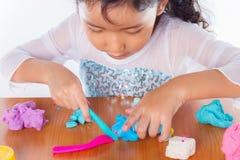 小女孩学会用五颜六色的戏剧面团 免版税库存图片