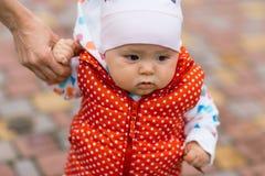 小女孩学会走,采取它的第一步 女性手母亲支持孩子 免版税库存图片