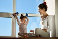 小女孩孩子在哑铃和微笑愉快地上升,炫耀他的成就对他的母亲 图库摄影