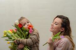 小女孩孩子,女儿给妈妈五颜六色的郁金香花花束-愉快的家庭 库存图片