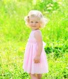 小女孩孩子晴朗的画象礼服的在草 免版税库存照片