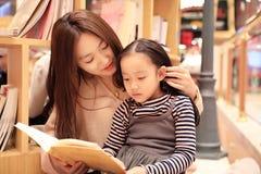 小女孩实践读书在精采地被阐明的市场上 免版税图库摄影
