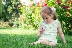 小女孩室外举行蝴蝶在她的手上 免版税库存图片