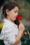 小女孩室外气味的玫瑰 图库摄影