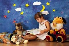 小女孩对她的读书故事充塞了玩具朋友 免版税图库摄影