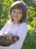 小女孩小农夫拿着一只母鸡 免版税库存图片