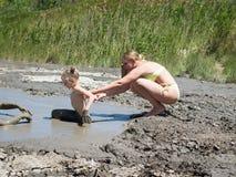 小女孩小心地下来在治疗做法的泥火山 免版税库存照片