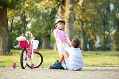 小女孩帮助有溜冰鞋的男孩站起来 免版税库存图片