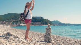 小女孩建造小卵石塔坐海滩由海 儿童` s梦想的概念 股票视频