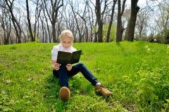 小女孩开会和读书在自然的一本书 免版税库存照片