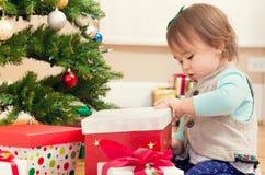 小女孩开头礼物在她的圣诞树下 免版税库存照片